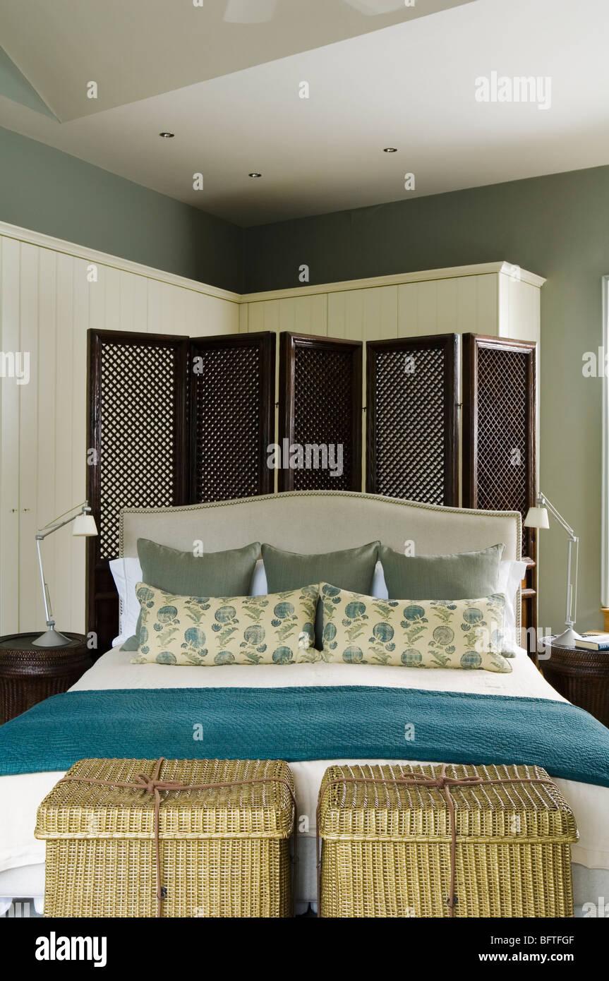 Chambre contemporain avec un lit double, paravent et d'unités de stockage Photo Stock
