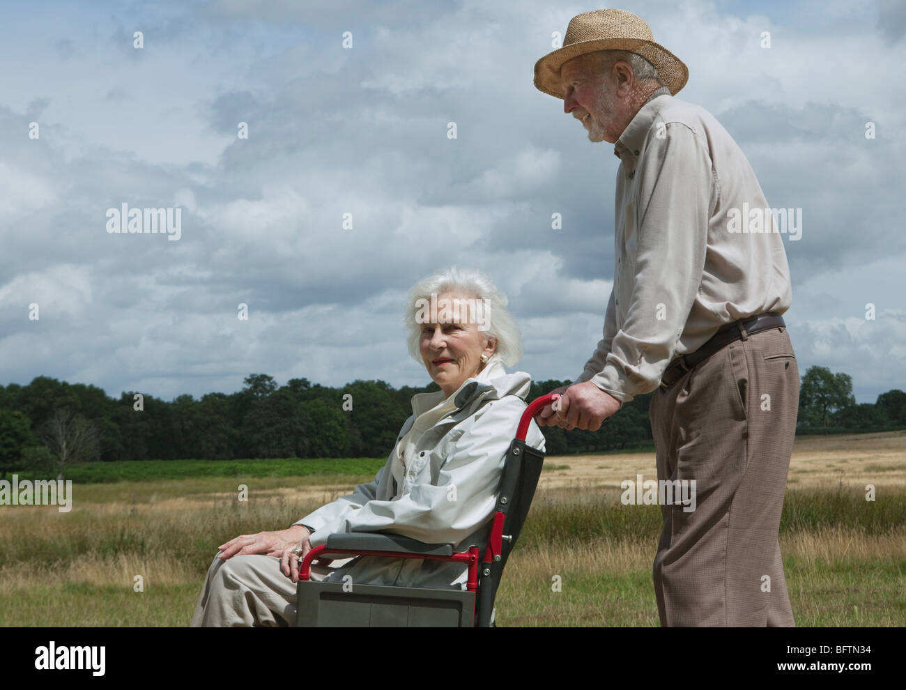 Personnes âgées man pushing woman in wheelchair Banque D'Images