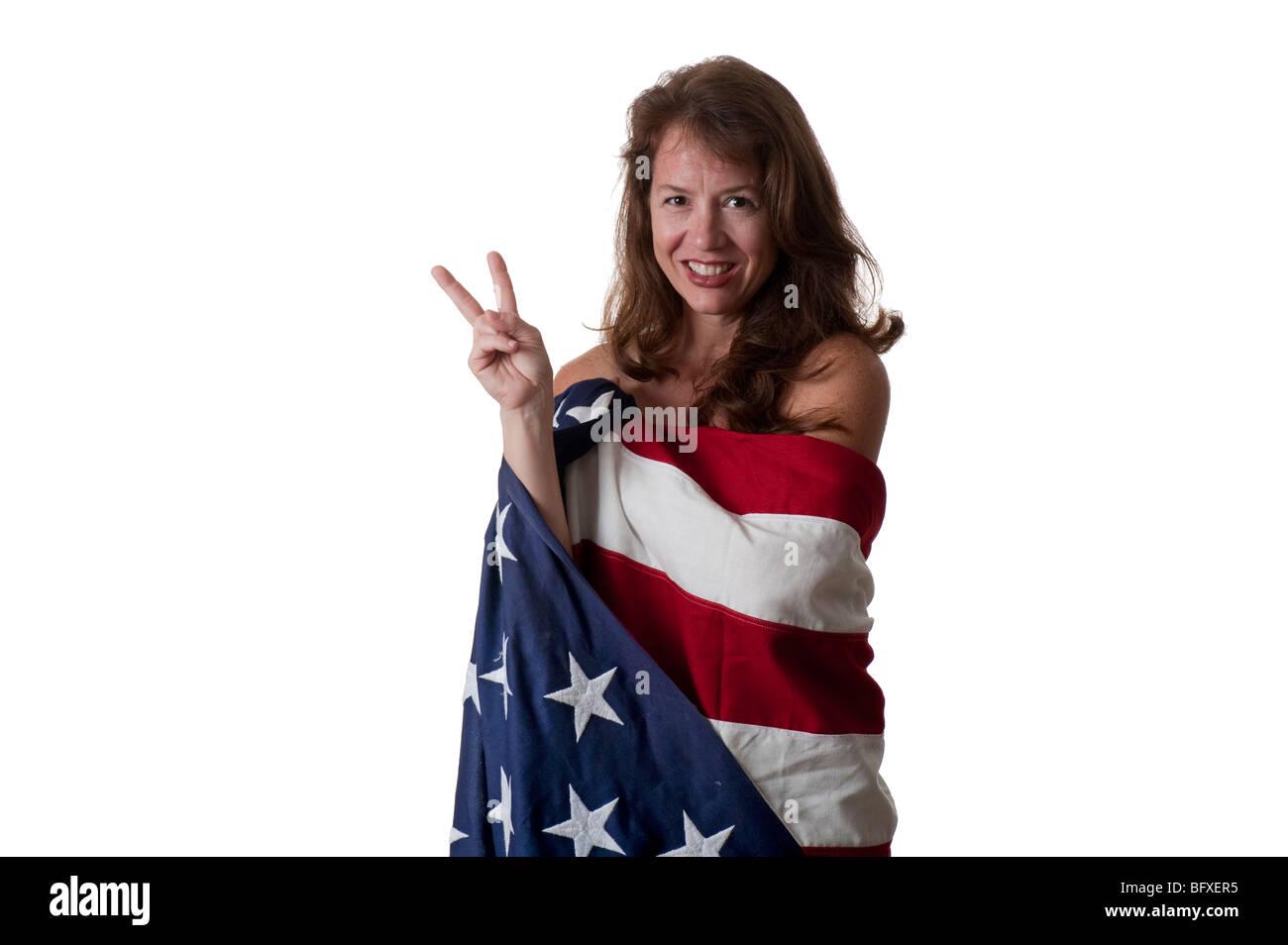 Belle jeune femme enveloppée dans un drapeau américain montrant signe de paix Photo Stock