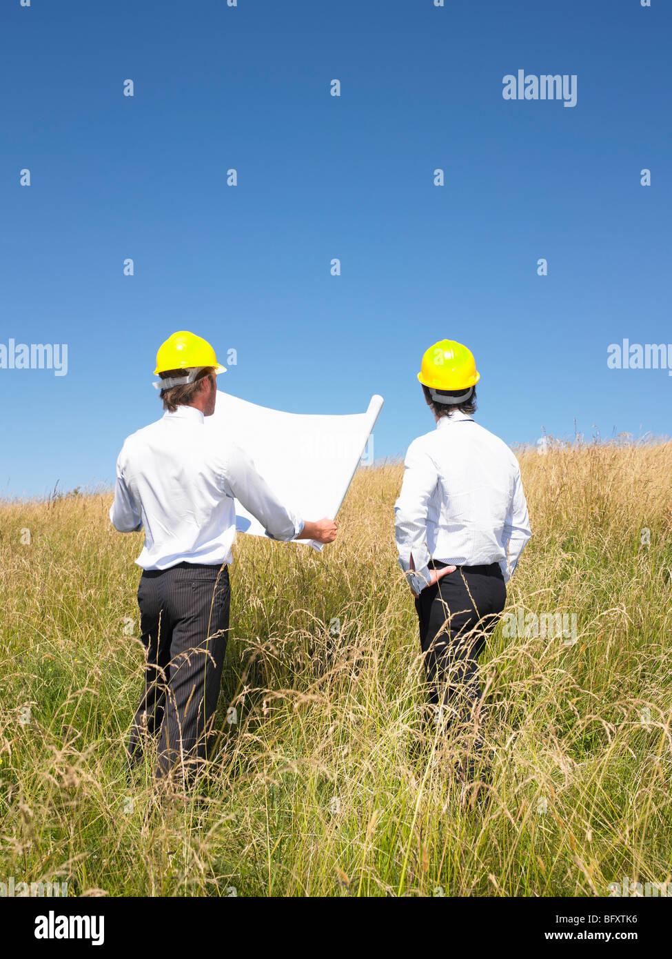 Les entrepreneurs avec les bleus dans le champ Photo Stock