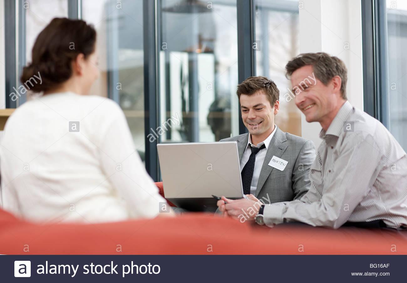 Les hommes et femmes ayant un rire au travail Banque D'Images