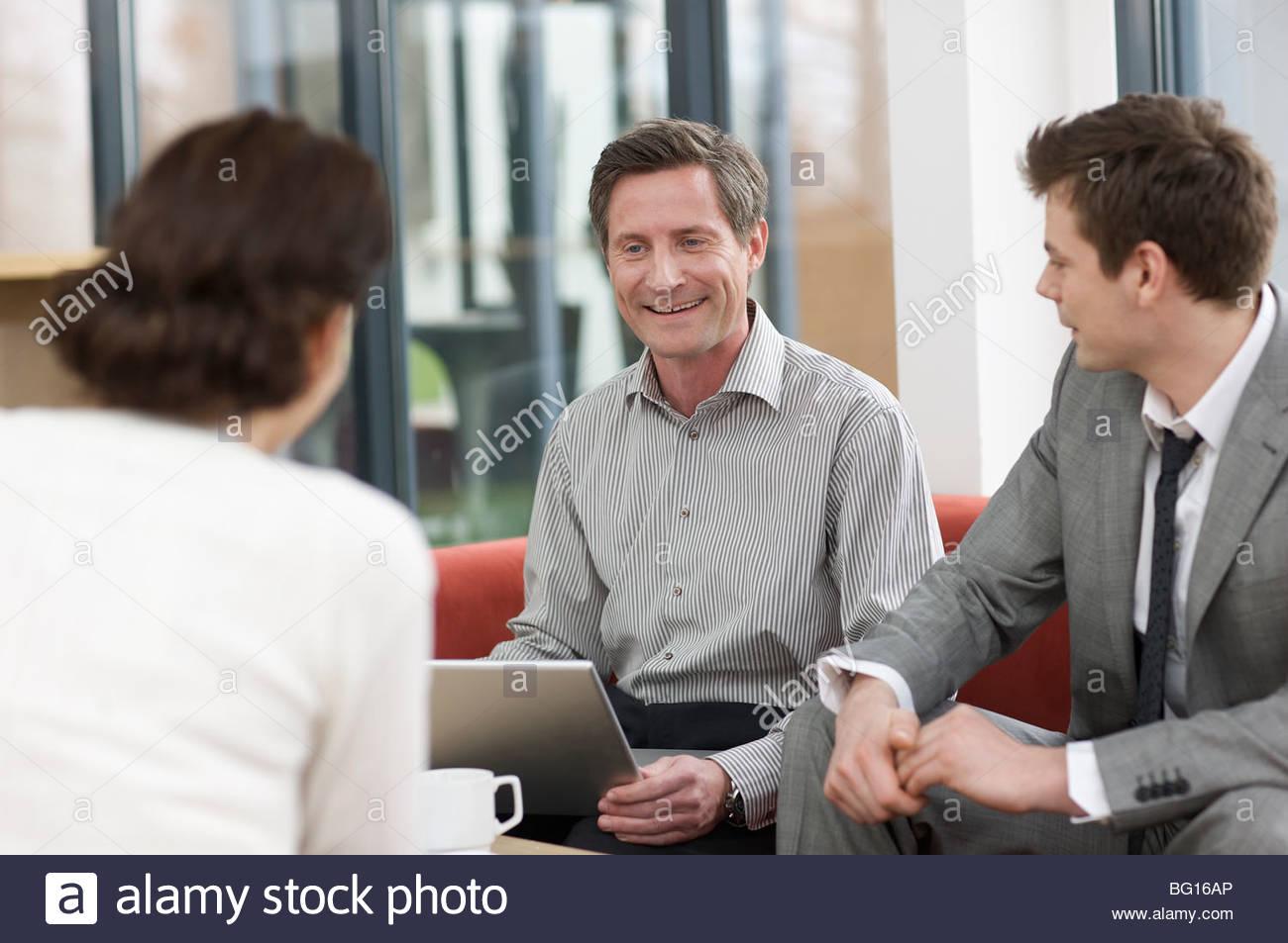 Les hommes et femmes ayant un rire au travail Photo Stock
