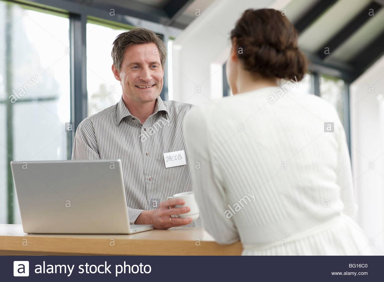 L'homme et la femme ayant un rire au travail Photo Stock