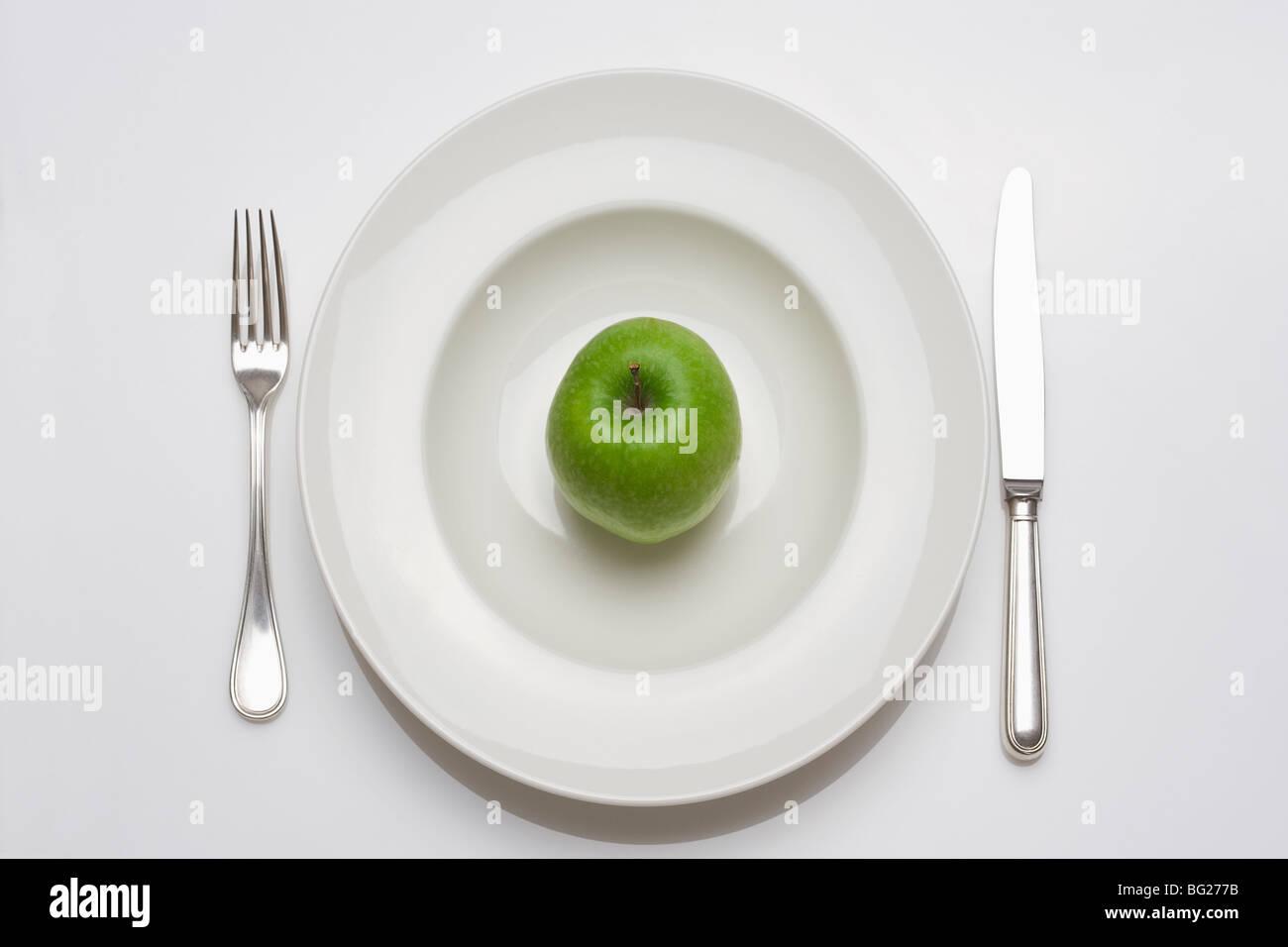 Régime alimentaire - pomme verte sur une plaque blanche avec fourchette et couteau Photo Stock