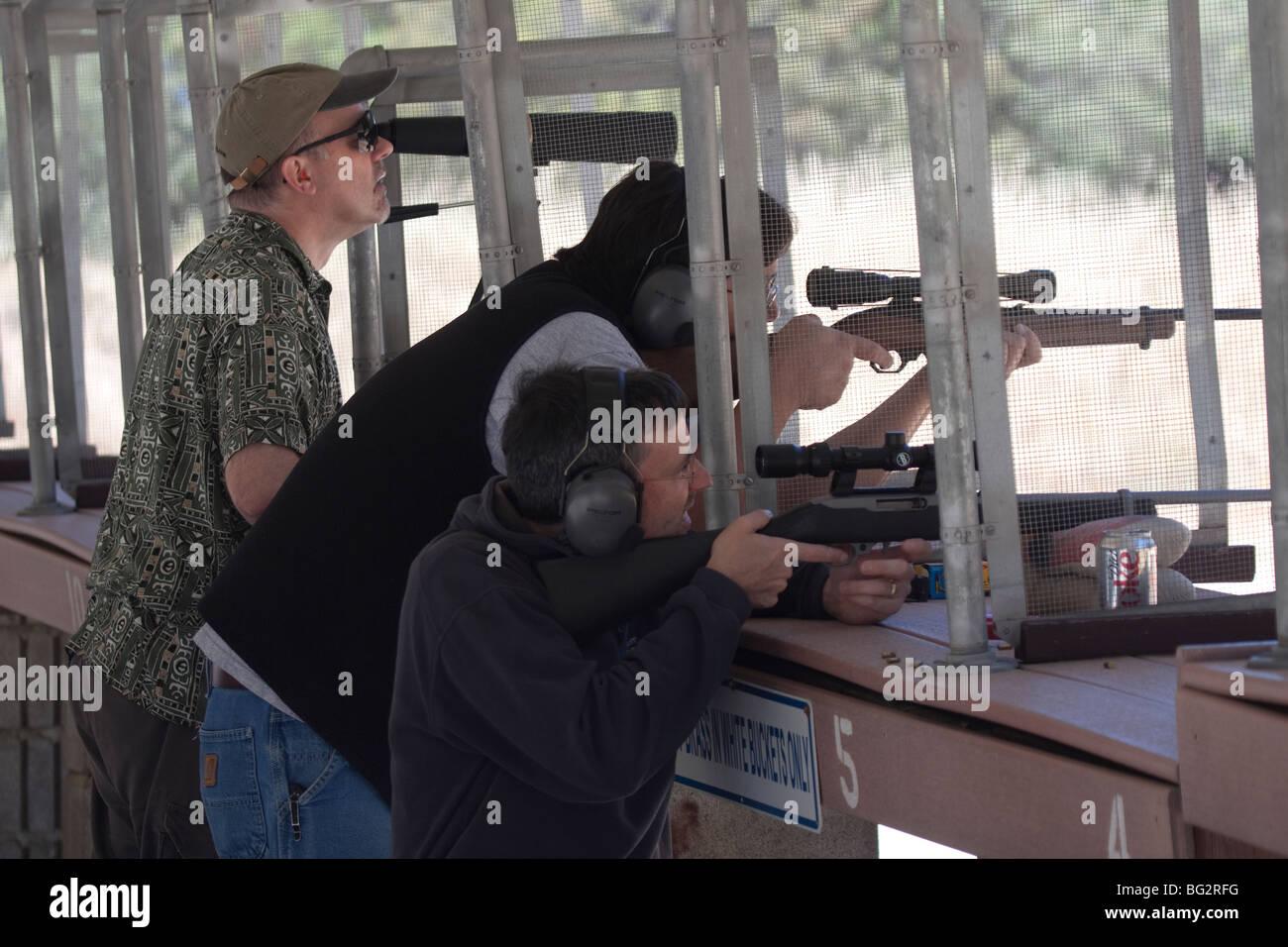 Trois hommes tir Ruger 10/22 rifles utilisation d'étendues au Los Altos Club de chasse et de tir en plein Photo Stock