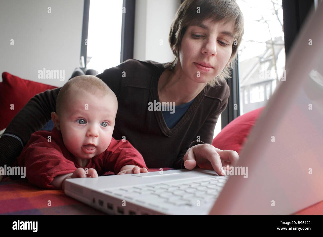 La mère et l'enfant le travail sur un ordinateur portable Banque D'Images