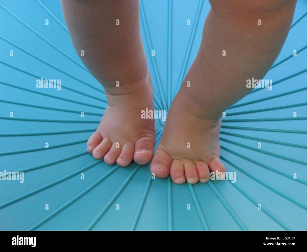 Les jambes et les pieds d'un enfant l'apprentissage de la marche dans un environnement bleu Photo Stock