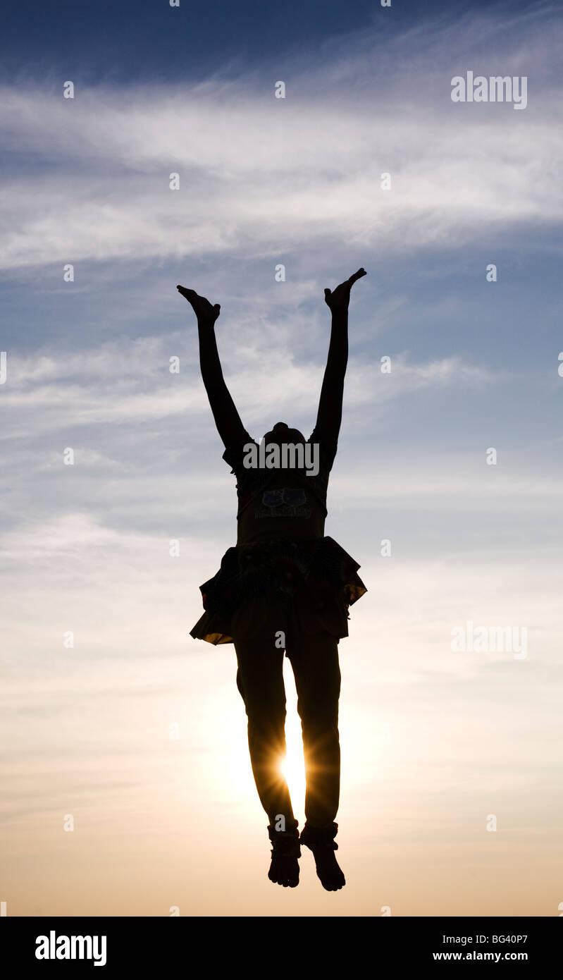 Silhouette d'une jeune Indienne sautant en l'air au coucher du soleil. L'Inde Photo Stock
