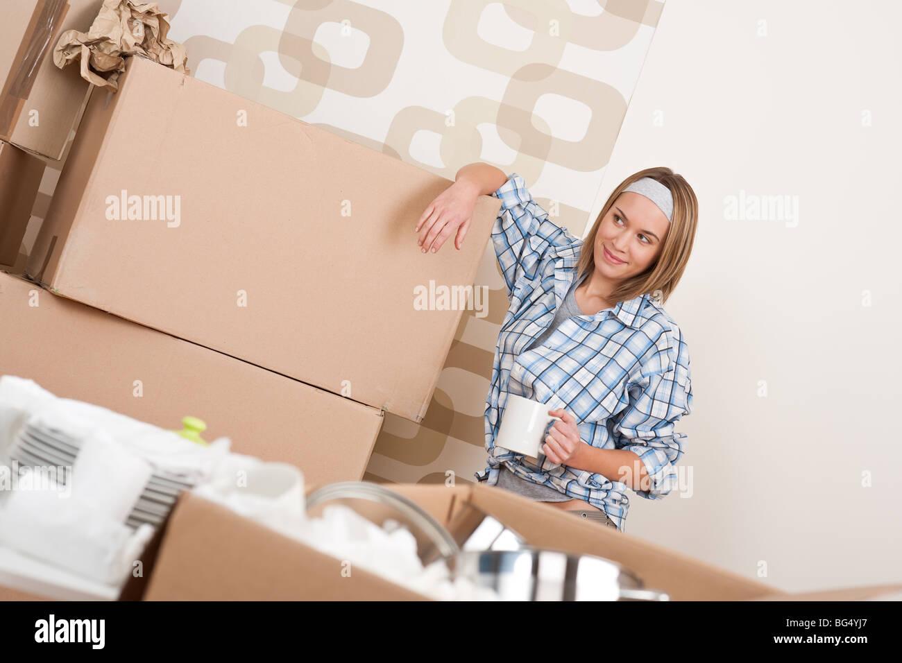 Déménagement - Happy woman holding box avec tasse de café in new home Photo Stock