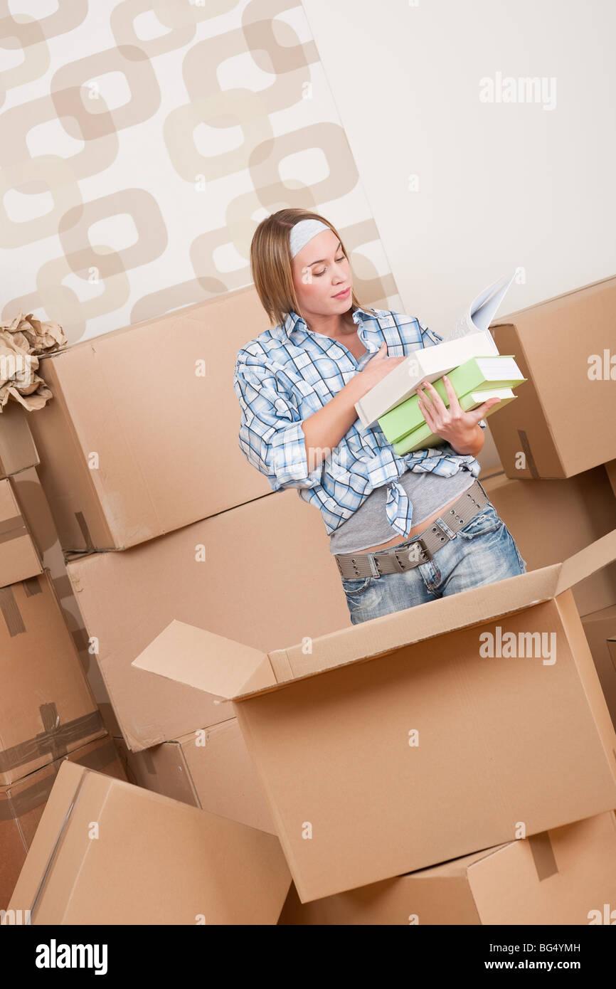 Déménagement - Woman unpacking fort avec réserve en nouvelle maison Photo Stock