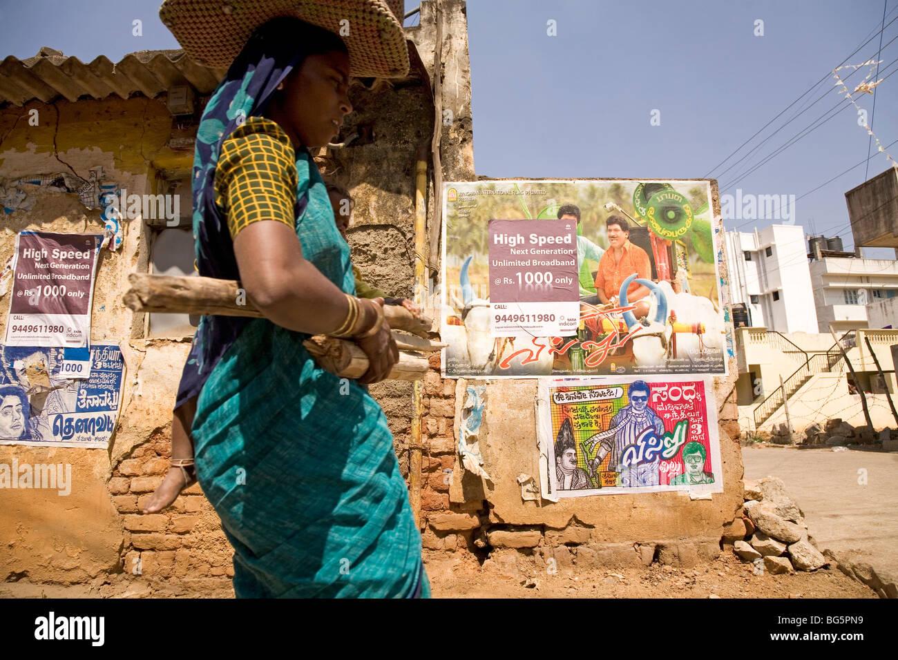 Une femme portant un bébé et du bois pour combustible passe devant un mur  portant des 09510fcf14f2