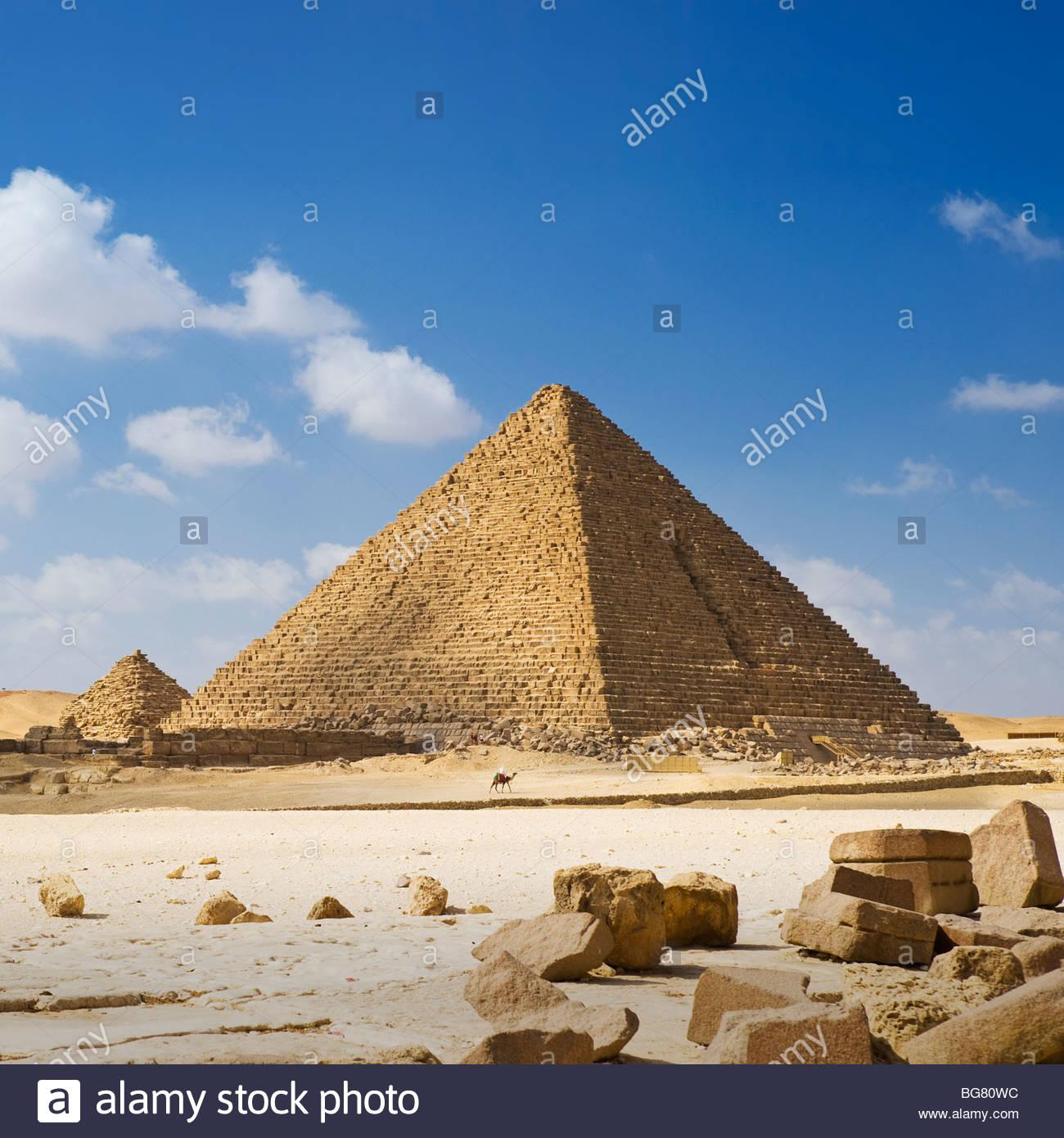 Un homme à dos de chameau est éclipsé par la Pyramide de Menkaourê, pyramides de Gizeh, Le Caire, Photo Stock