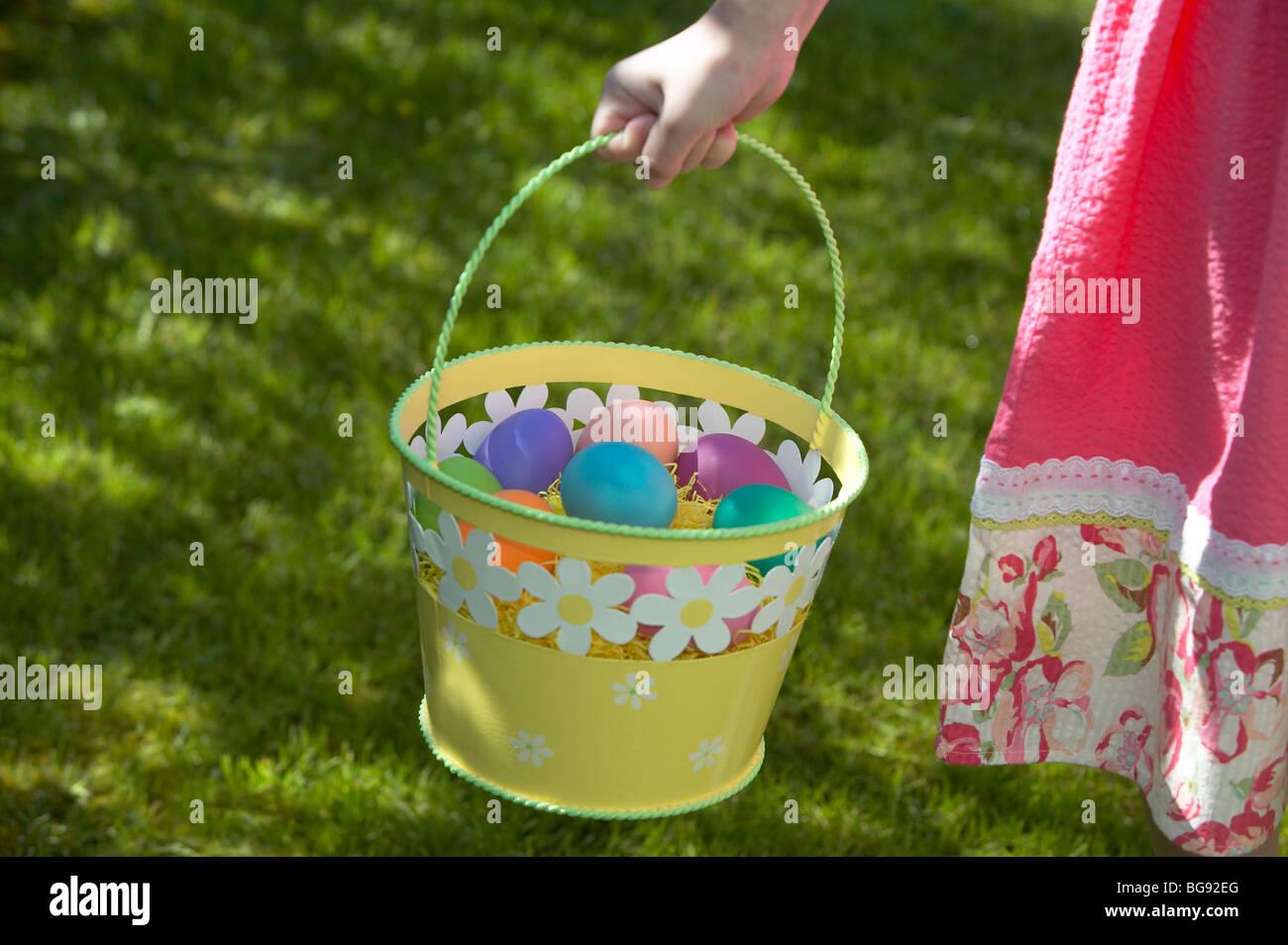 Girl holding easter egg dans panier en marchant sur la pelouse Photo Stock