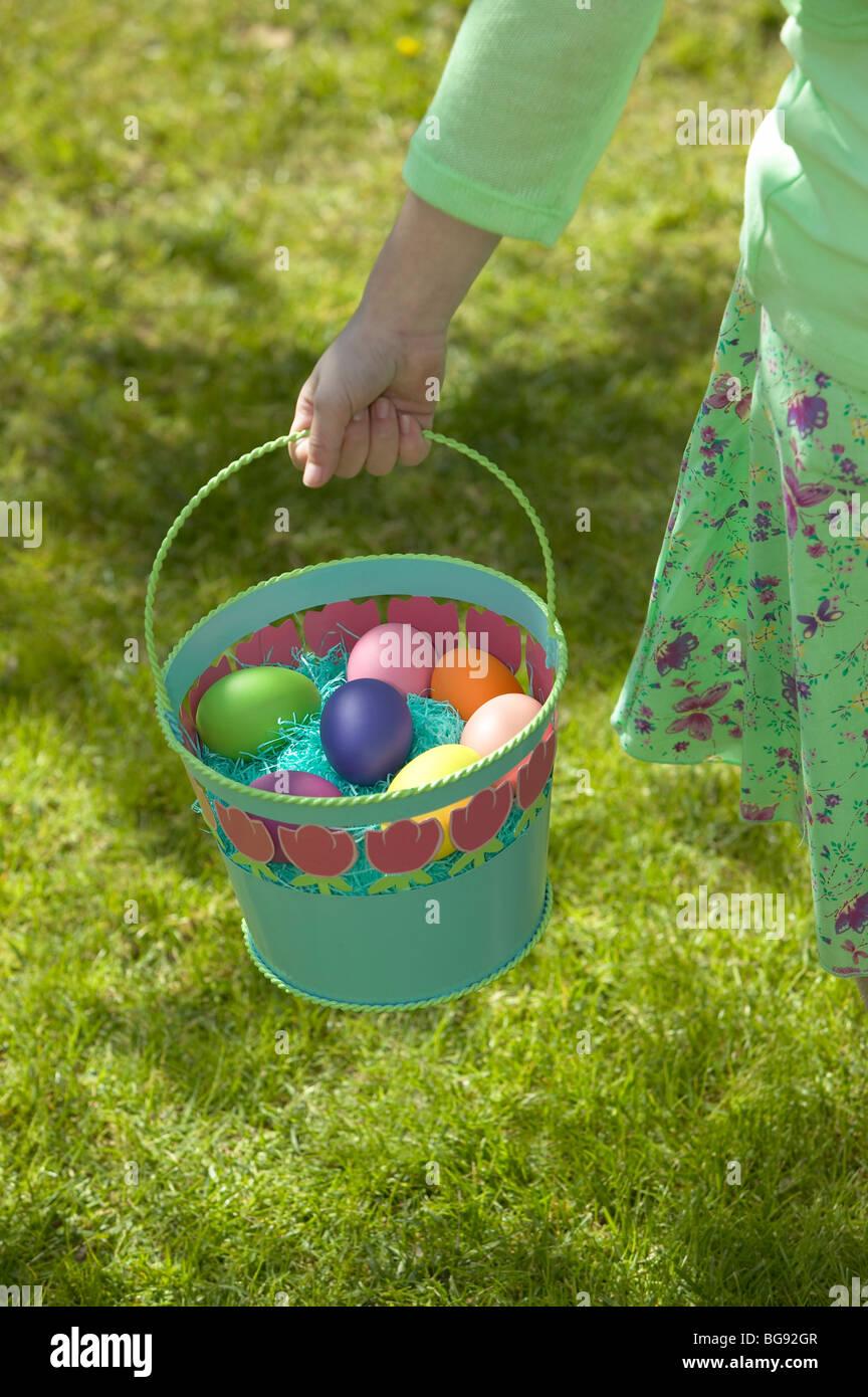Girl holding easter egg basket en marchant sur la pelouse Photo Stock