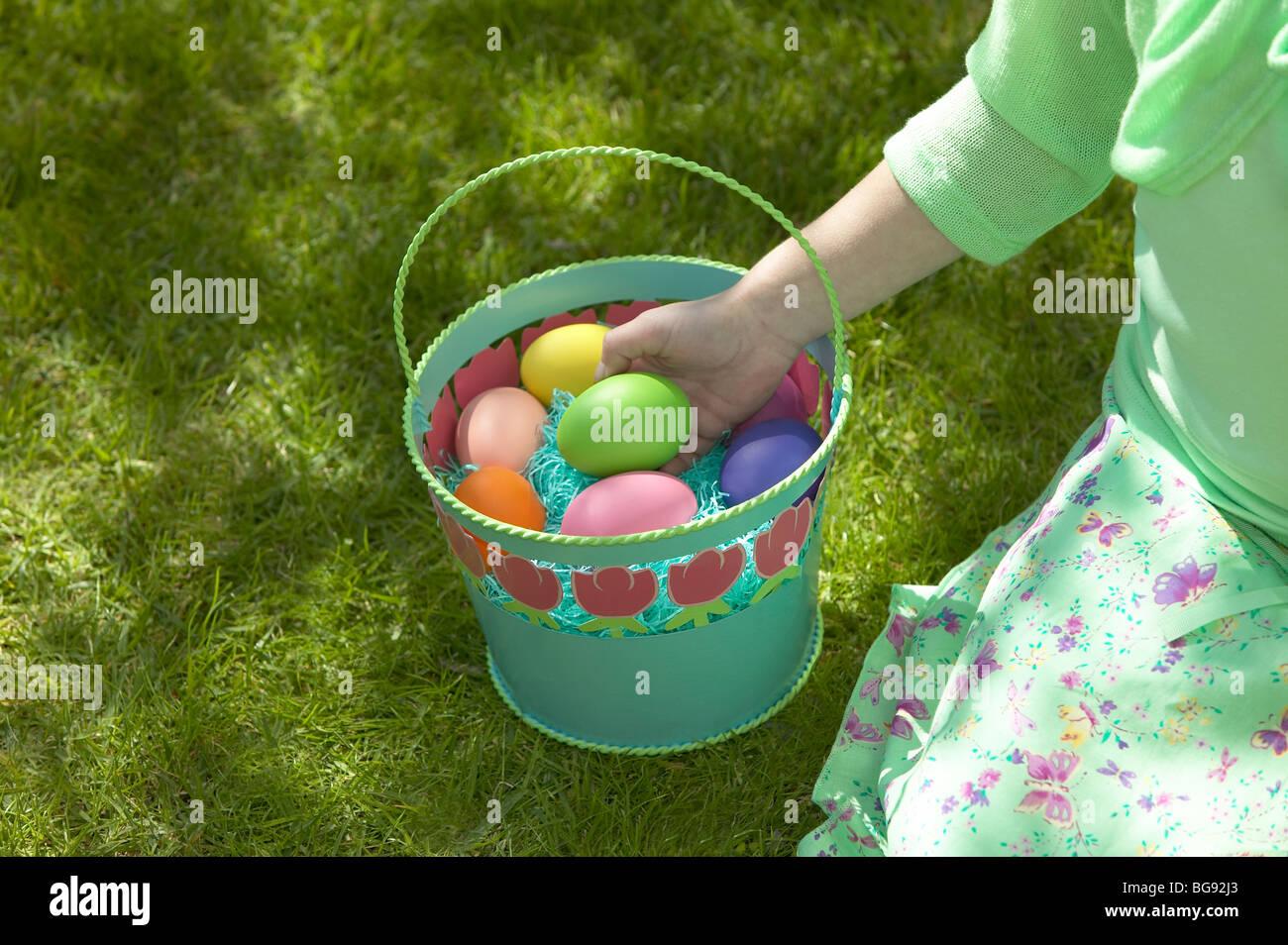Girl holding easter egg dans panier tout en étant assis sur la pelouse Photo Stock