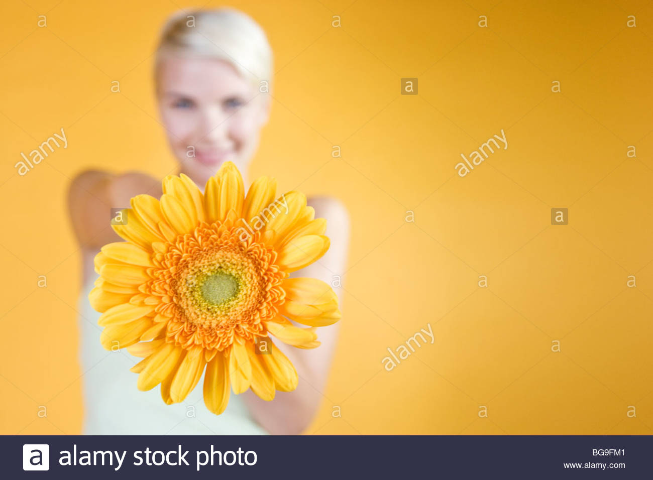 Une jeune femme tenant une fleur orange Photo Stock