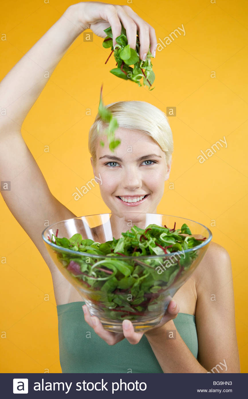 Une jeune femme tenant un bol de salade Photo Stock