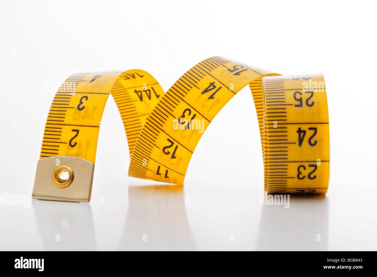 Alimentation - mètre à ruban jaune isolé sur fond blanc Photo Stock