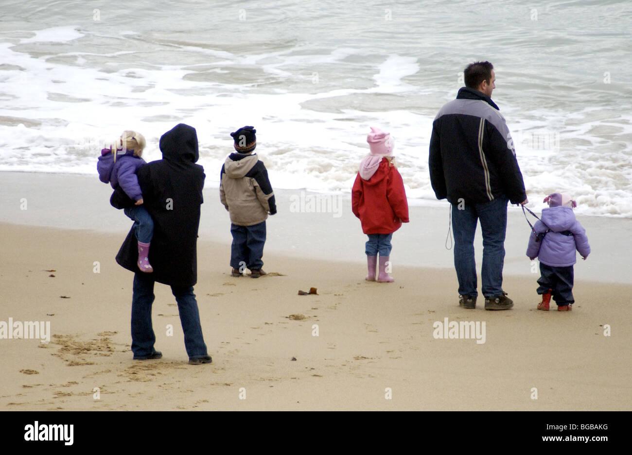 Famille sur la plage face à la mer Banque D'Images