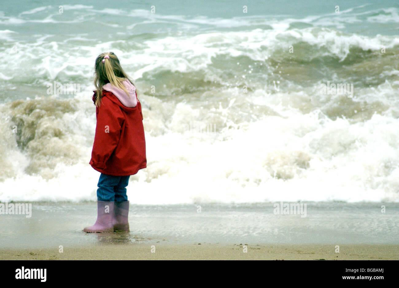 Jeune fille à la recherche à une grosse vague sur la plage en hiver. Banque D'Images