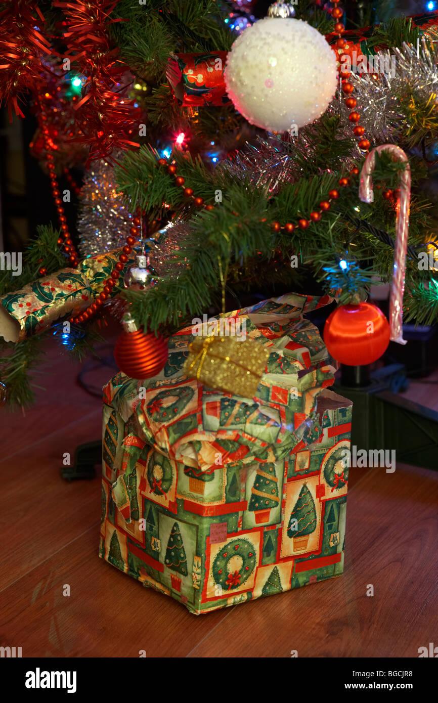 Mal emballé seul cadeau de Noël sous le sapin de Noël à Noël au Royaume-Uni Banque D'Images