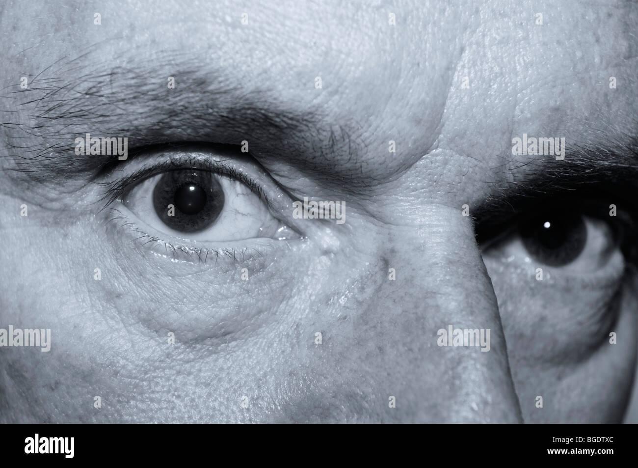 Sinister à close up d'un vieux Mans yeux en monochrome Photo Stock