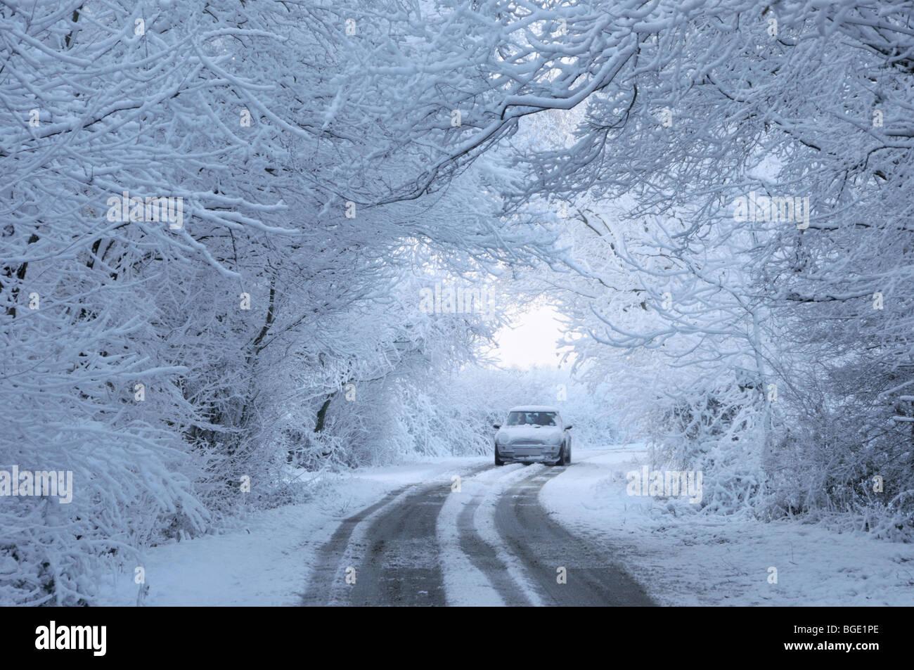 Location de voiture sur la neige a couvert country lane Banque D'Images