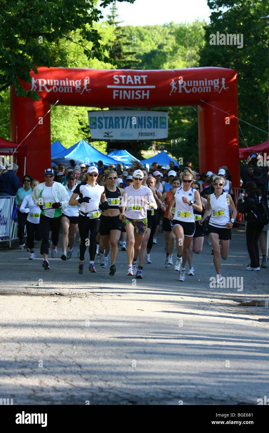 Coureur de marathon féminin porteur la concurrence Photo Stock
