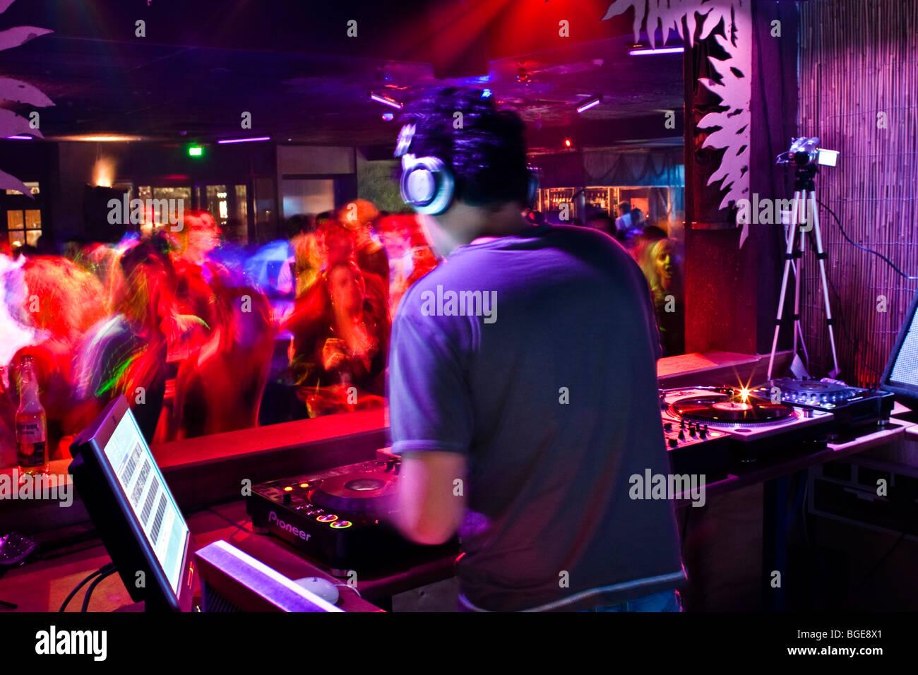 Mixage DJ dans une boîte de nuit remplie de danseurs Photo Stock