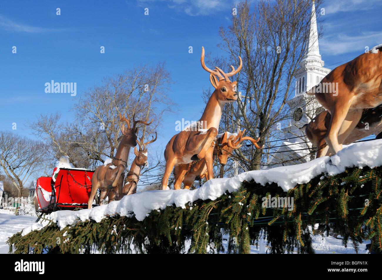 Le traîneau du Père Noël et des rennes à Noël avec la neige et le clocher de l'église et ciel bleu Banque D'Images
