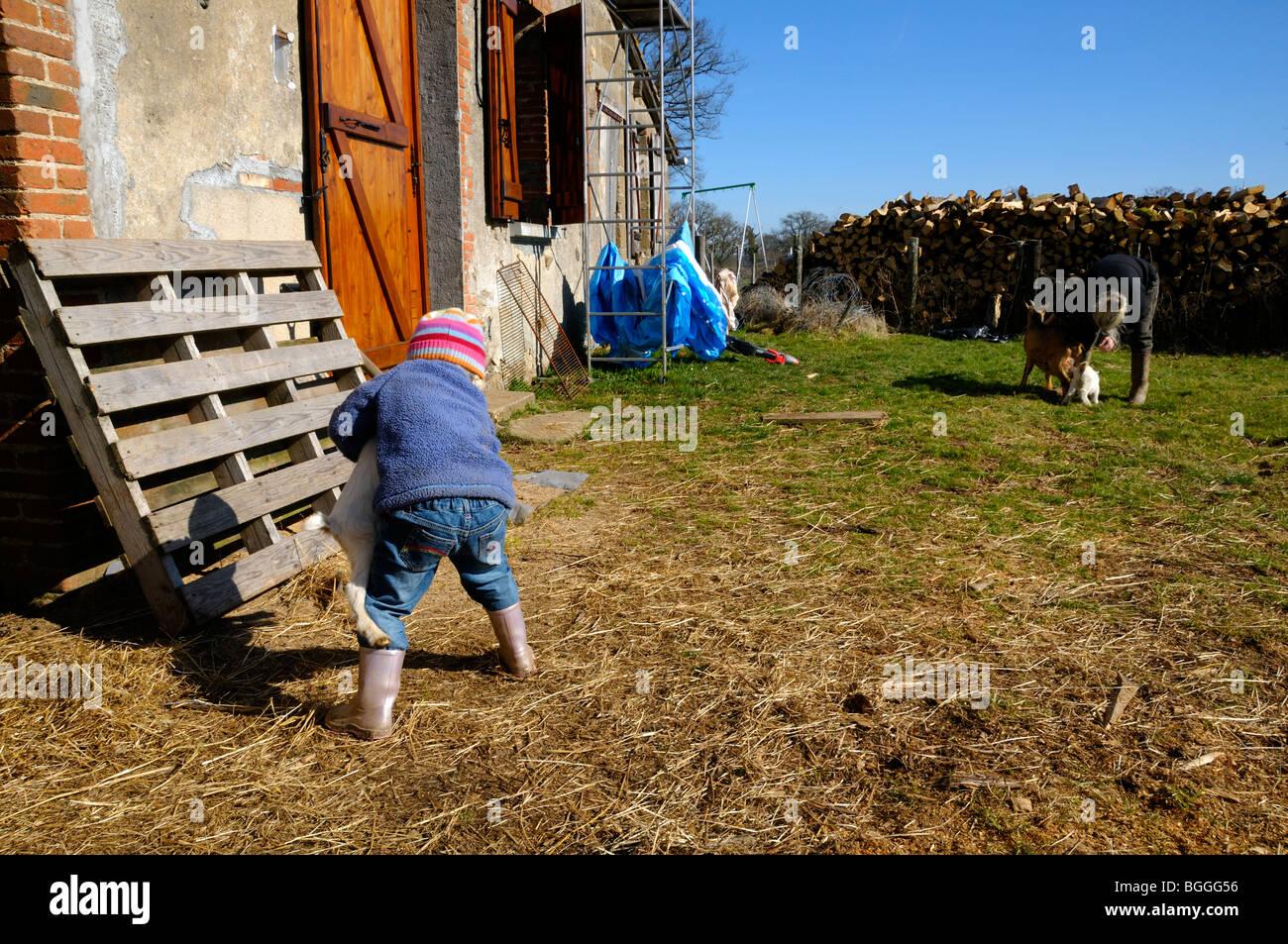 Stock photo d'une fillette de 3 ans aider sa mère avec les chèvres, dans les lopins de familles. Banque D'Images