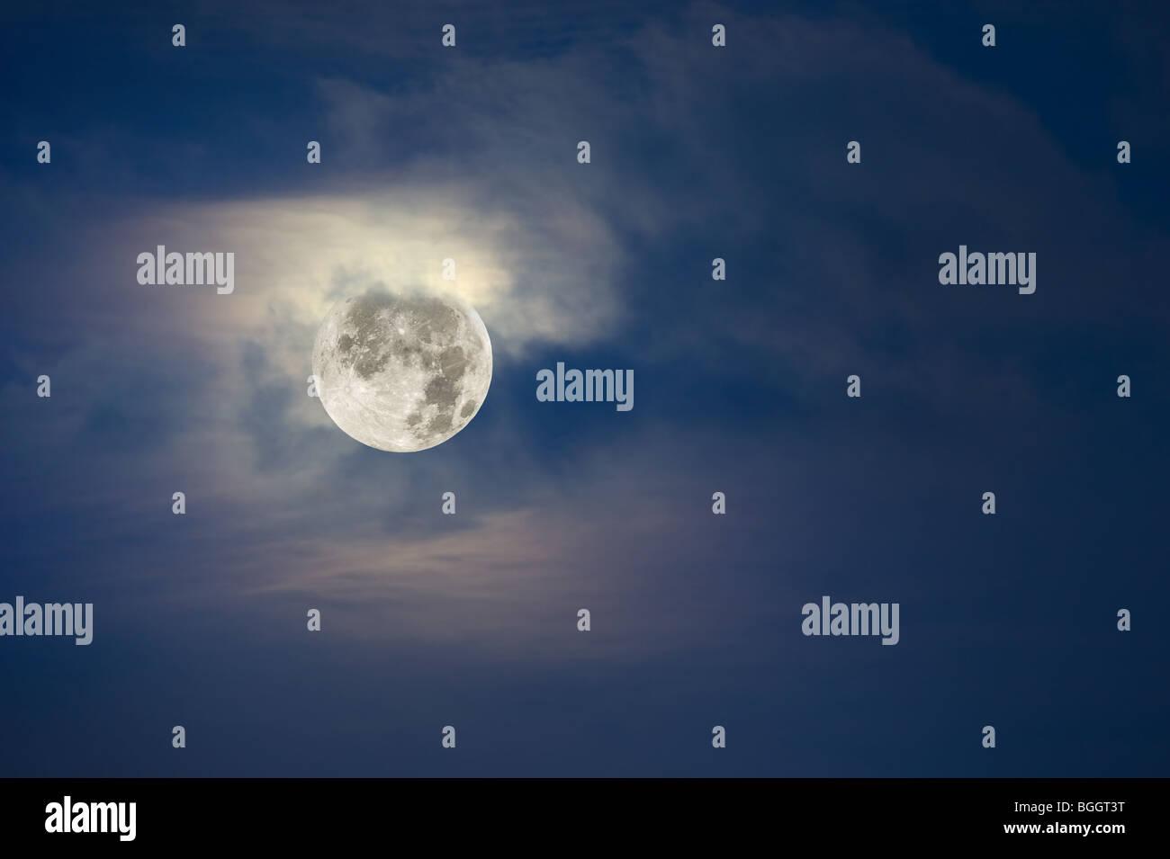 Une pleine lune lumineuse s'allume le temps nuageux, ciel. Photo Stock