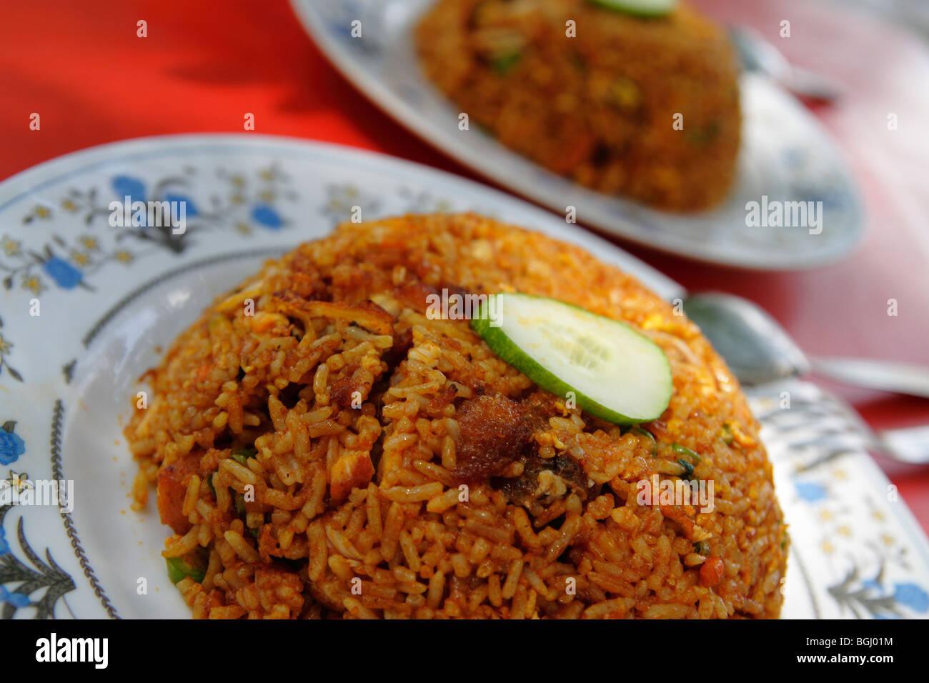 Deux plaques de riz frit avec du poulet et concombre Photo Stock