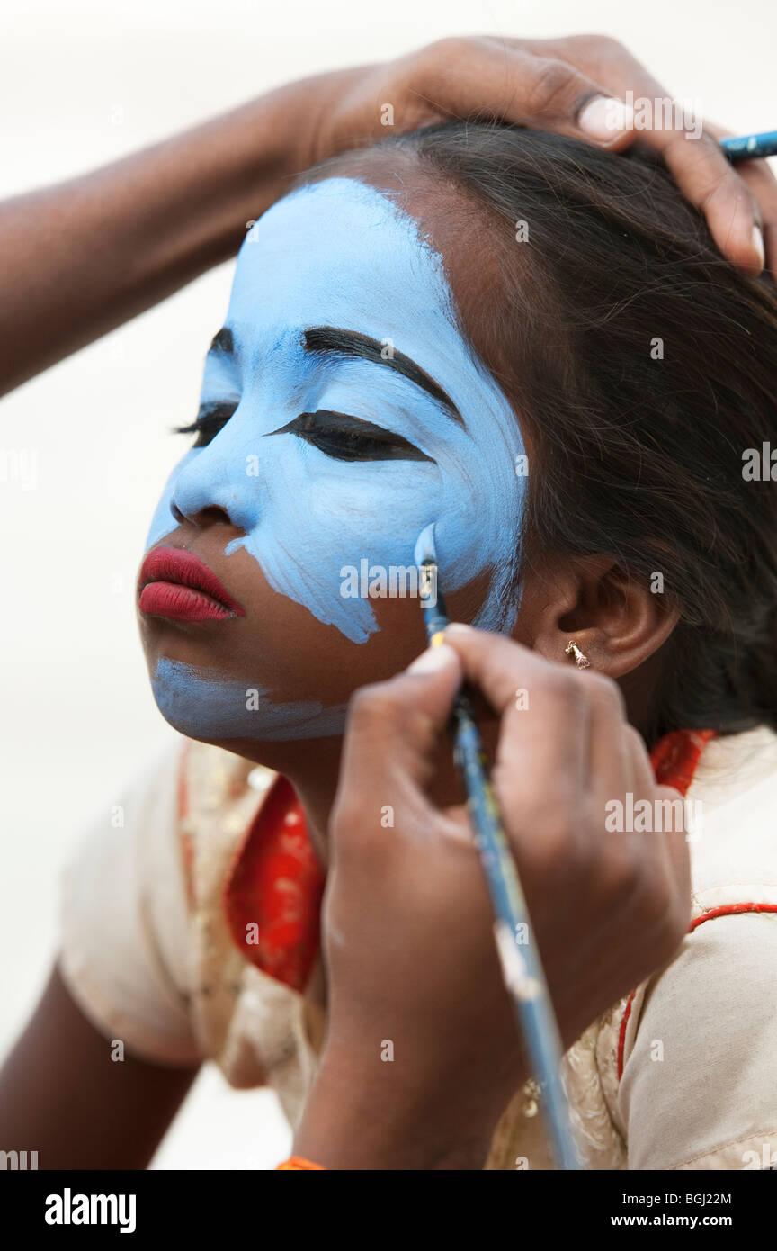 Indian girl ayant son visage peint en bleu pour être constitué comme une divinité de l'Inde. Photo Stock