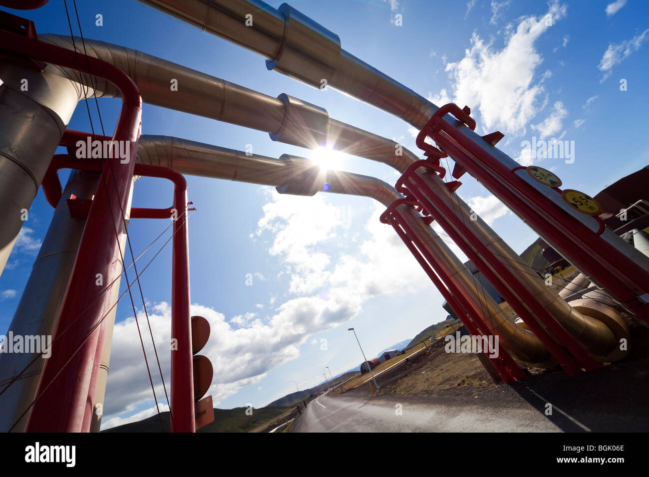 Tuyaux industriels et des pipelines et détournés sur une route pour permettre le trafic de passer en dessous. Photo Stock