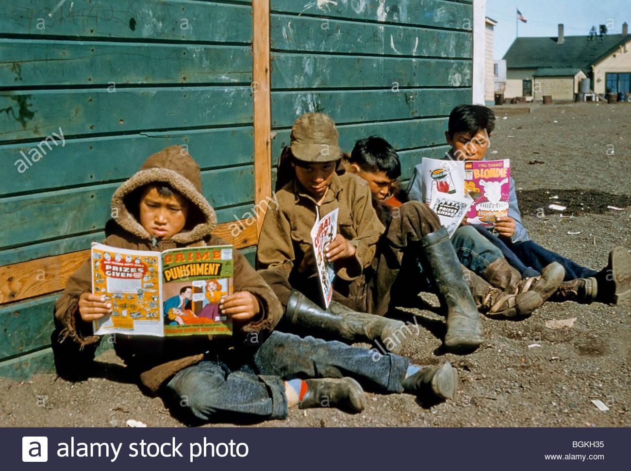 Alaska, Barrow. Les garçons Inupiaq la lecture des bandes dessinées. Circa 1948. Photo Stock
