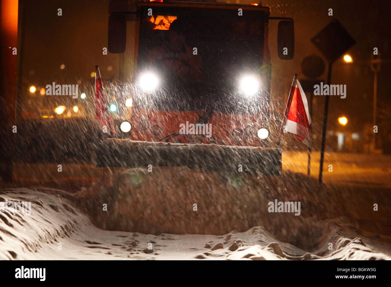 Enlever la neige chasse-neige sur un trottoir dans les fortes chutes de neige à soir Banque D'Images