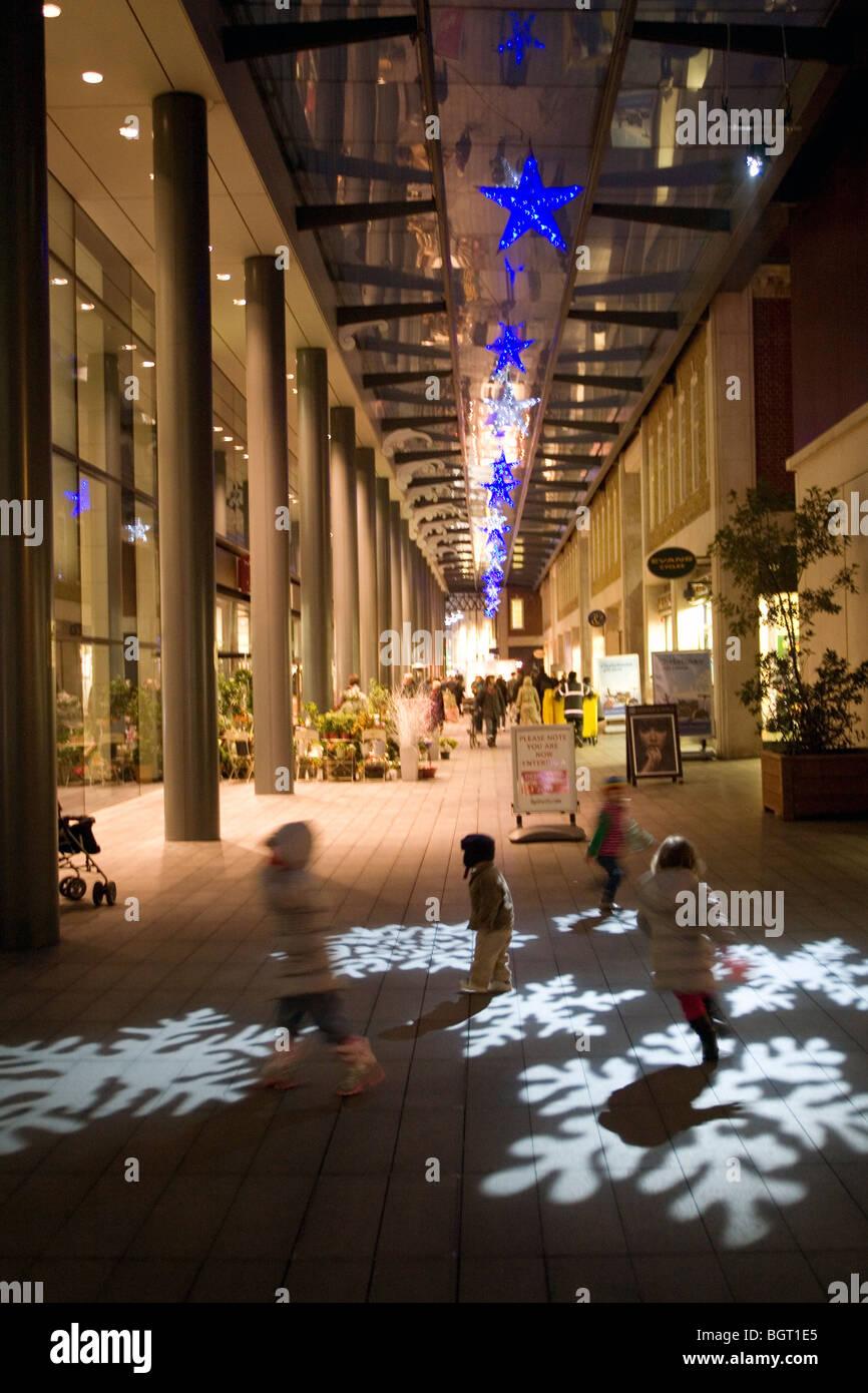 Les enfants courent le plus de lumières de Noël projeté sur la chaussée Spitalfields Londres, Photo Stock