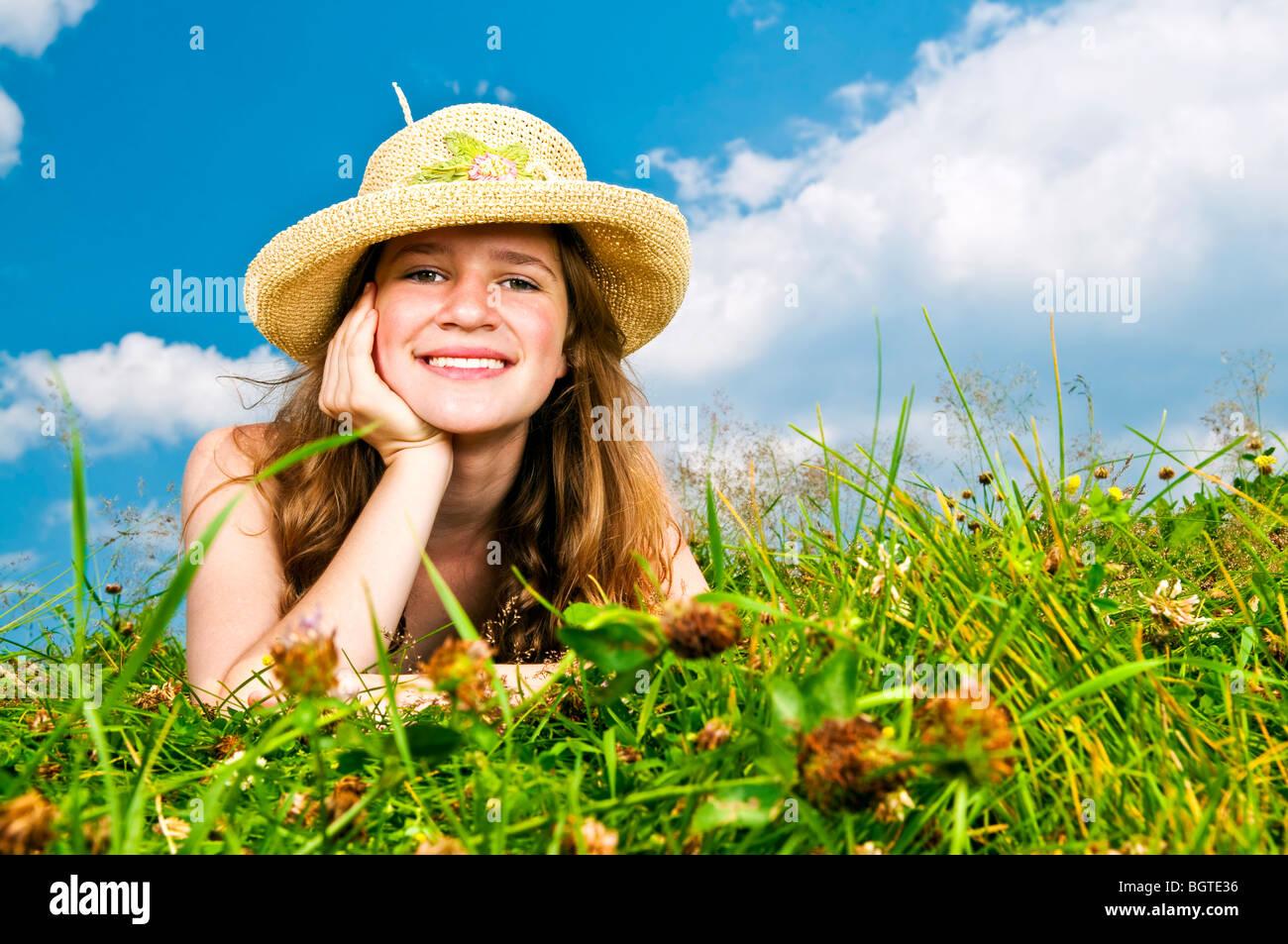 Young woman laying in summer meadow de repos en chapeau de paille Banque D'Images