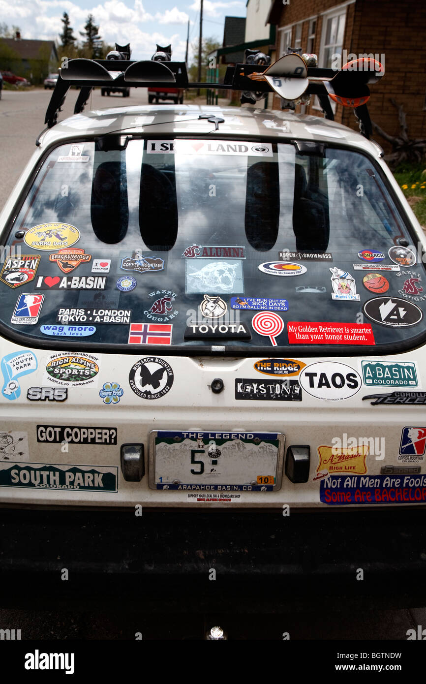 Vue arrière dune petite voiture blanche toyota avec de nombreux badges et autocollants et skis sur barre de toit retirer la plaque de licence