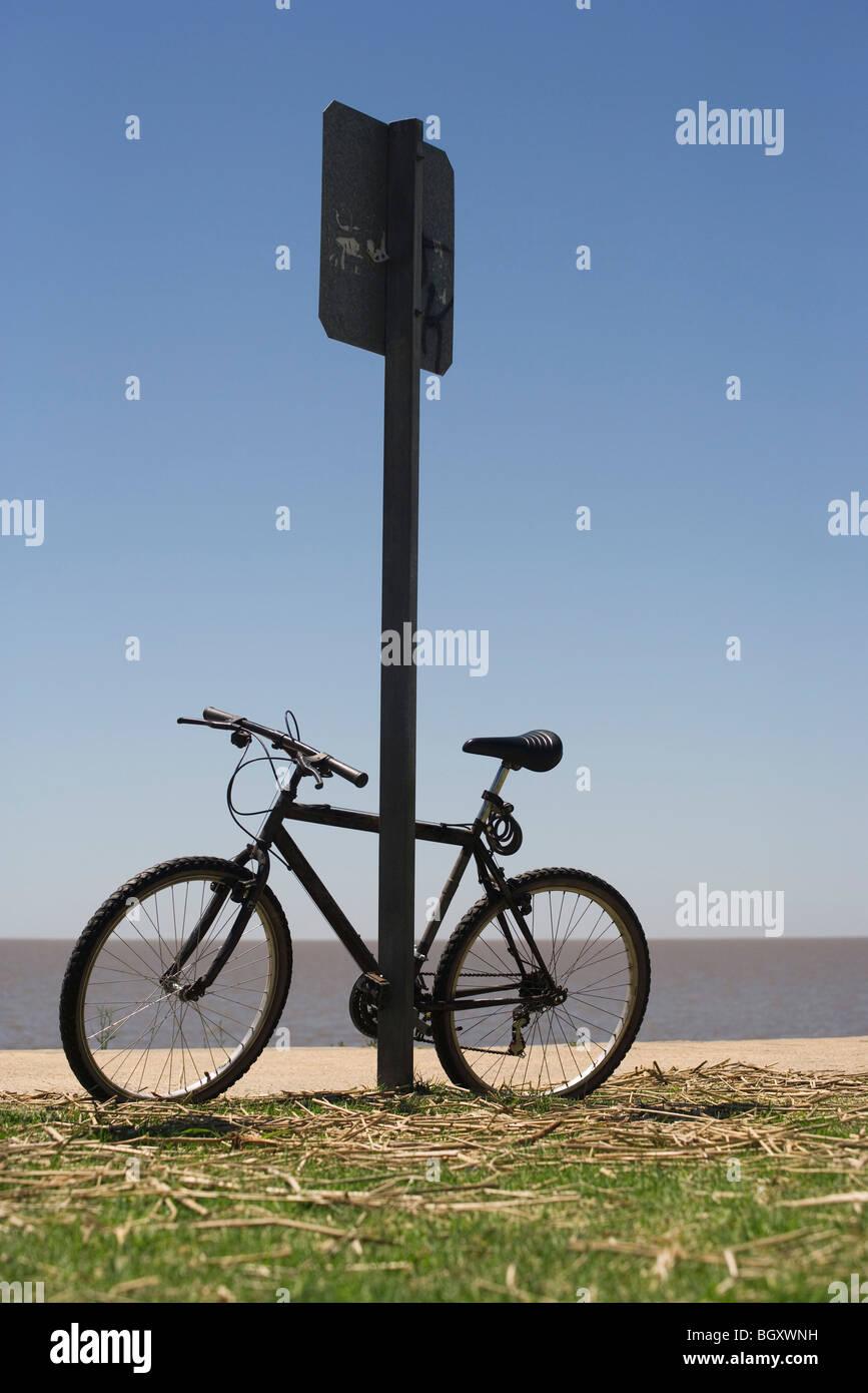 Bicycle leaning against street sign, plage en arrière-plan Banque D'Images