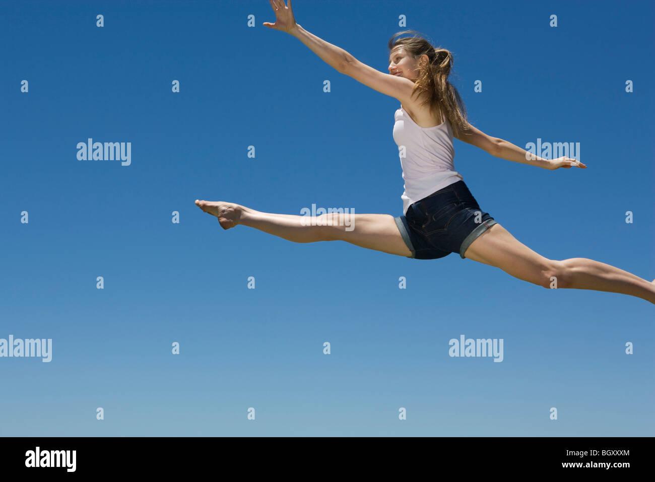 Jeune femme sautant, plein ciel Banque D'Images