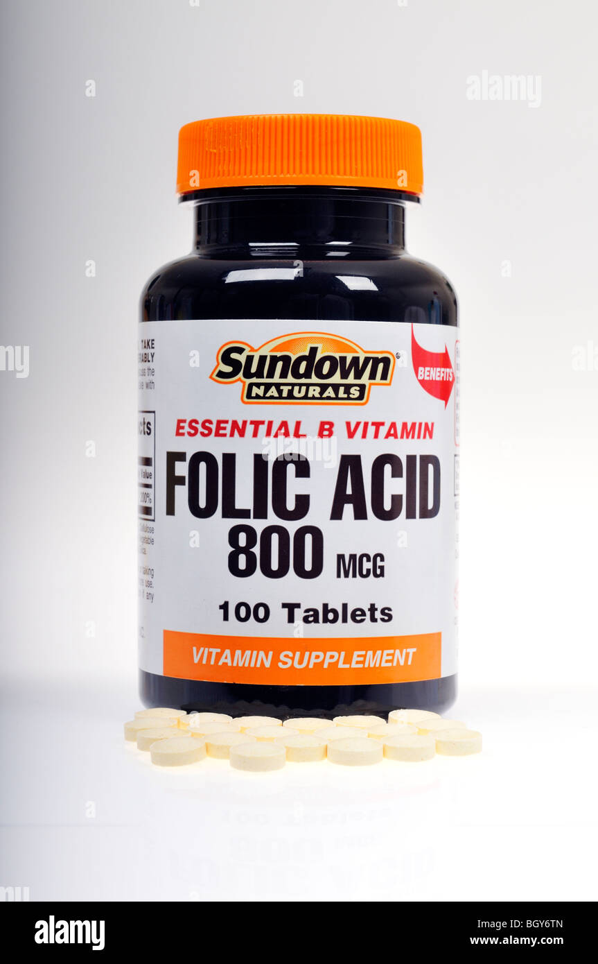 Un flacon non ouvert de Sundown Naturals vitamines Acide folique avec certaines pilules renversé sur fond blanc. Photo Stock