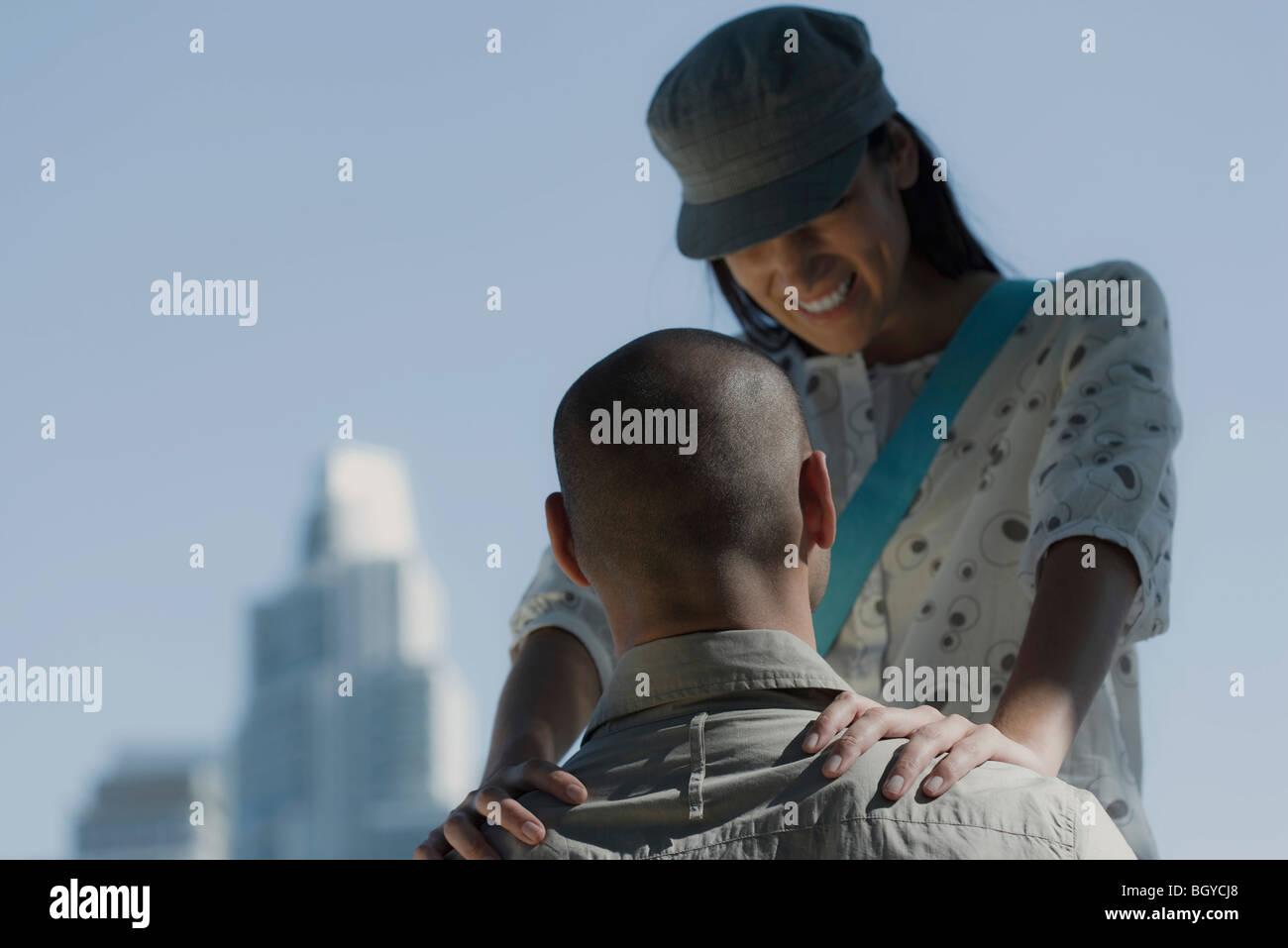 Jeune couple, l'homme assis, femme debout à l'avant avec les mains placées sur les épaules Photo Stock