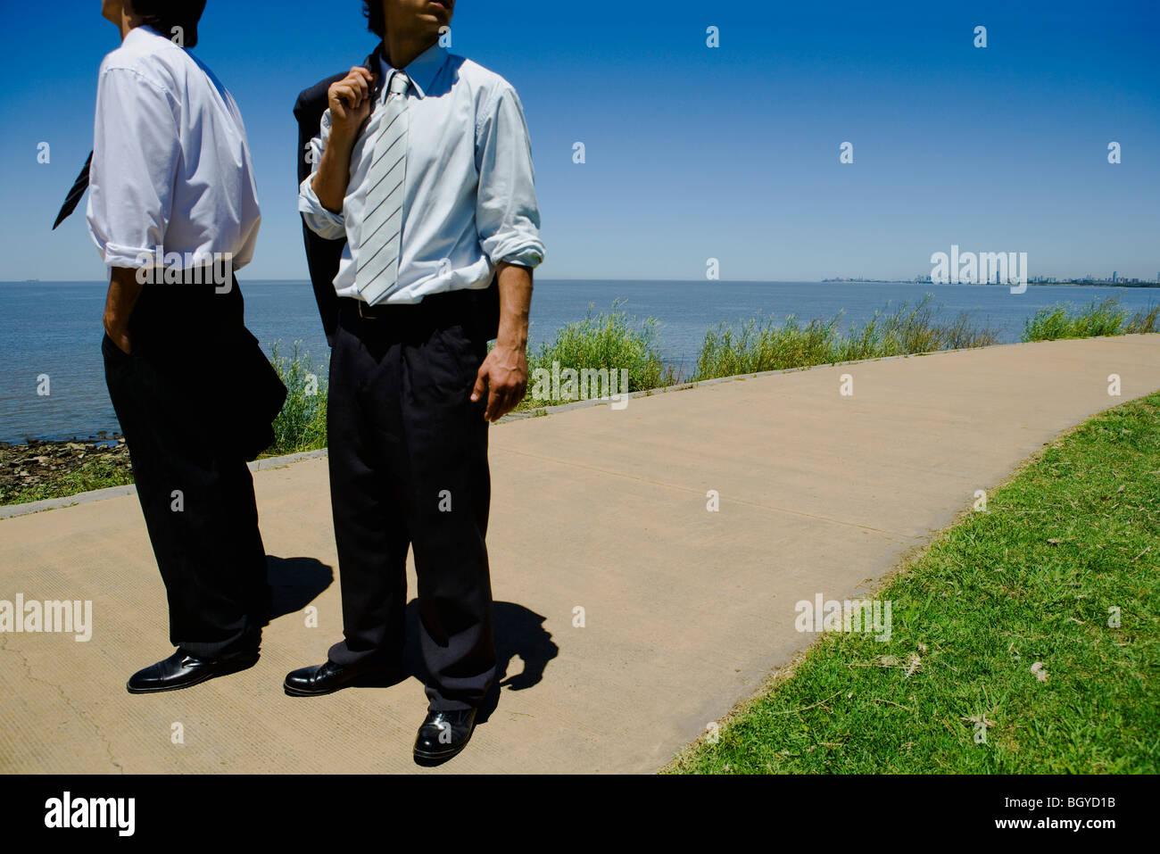 Deux jeunes hommes debout sur chemin, mer en arrière-plan, cropped Photo Stock