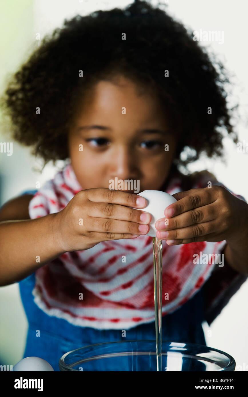 Petite fille dans le bol d'oeufs de fissuration Photo Stock