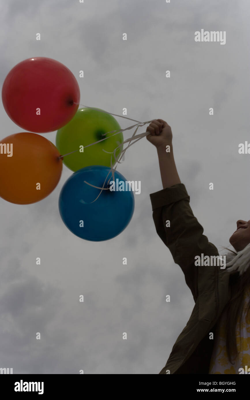 Femme holding bunch of balloons vers ciel nuageux Photo Stock
