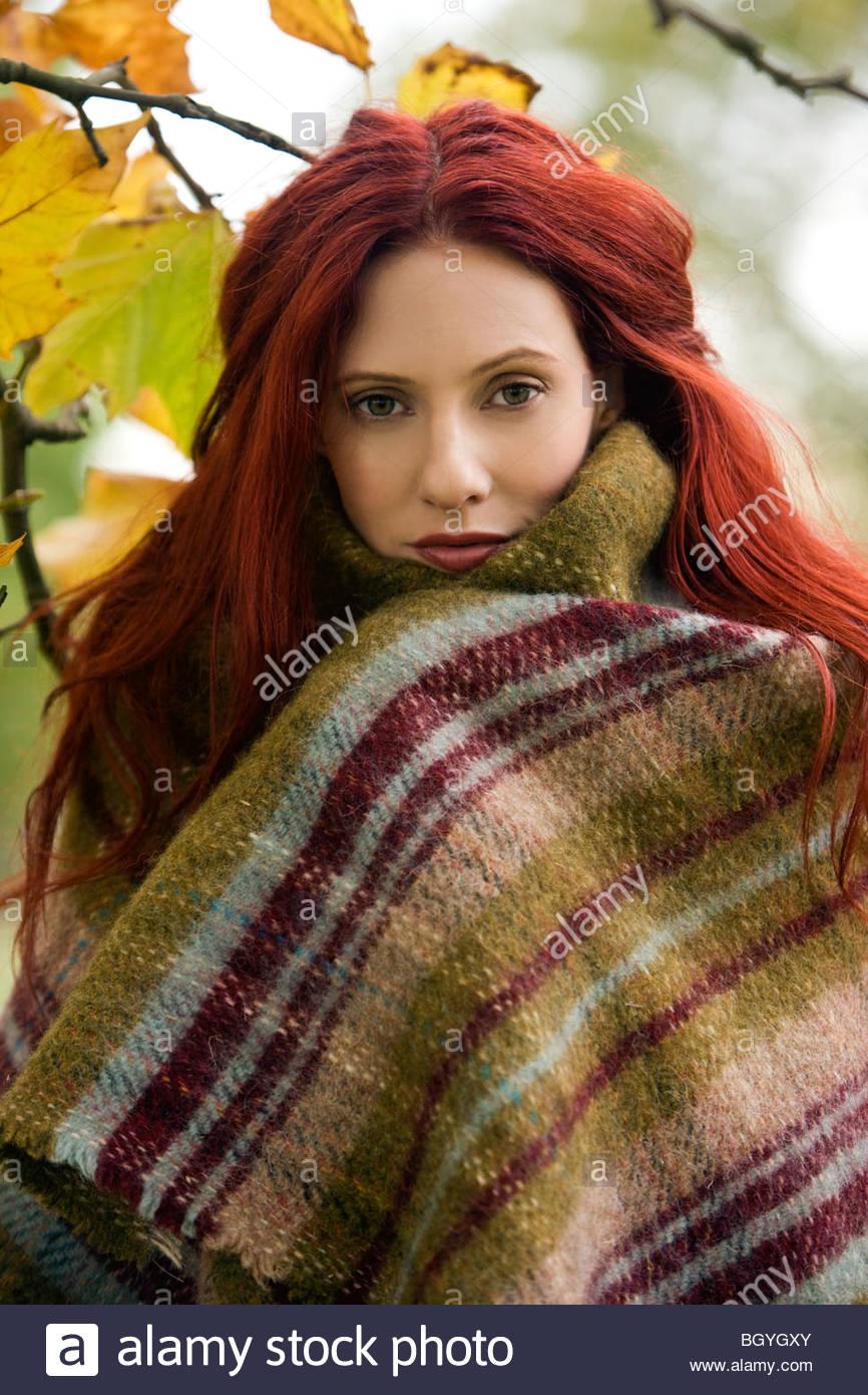 Portrait d'une jeune femme enveloppée dans une couverture Photo Stock