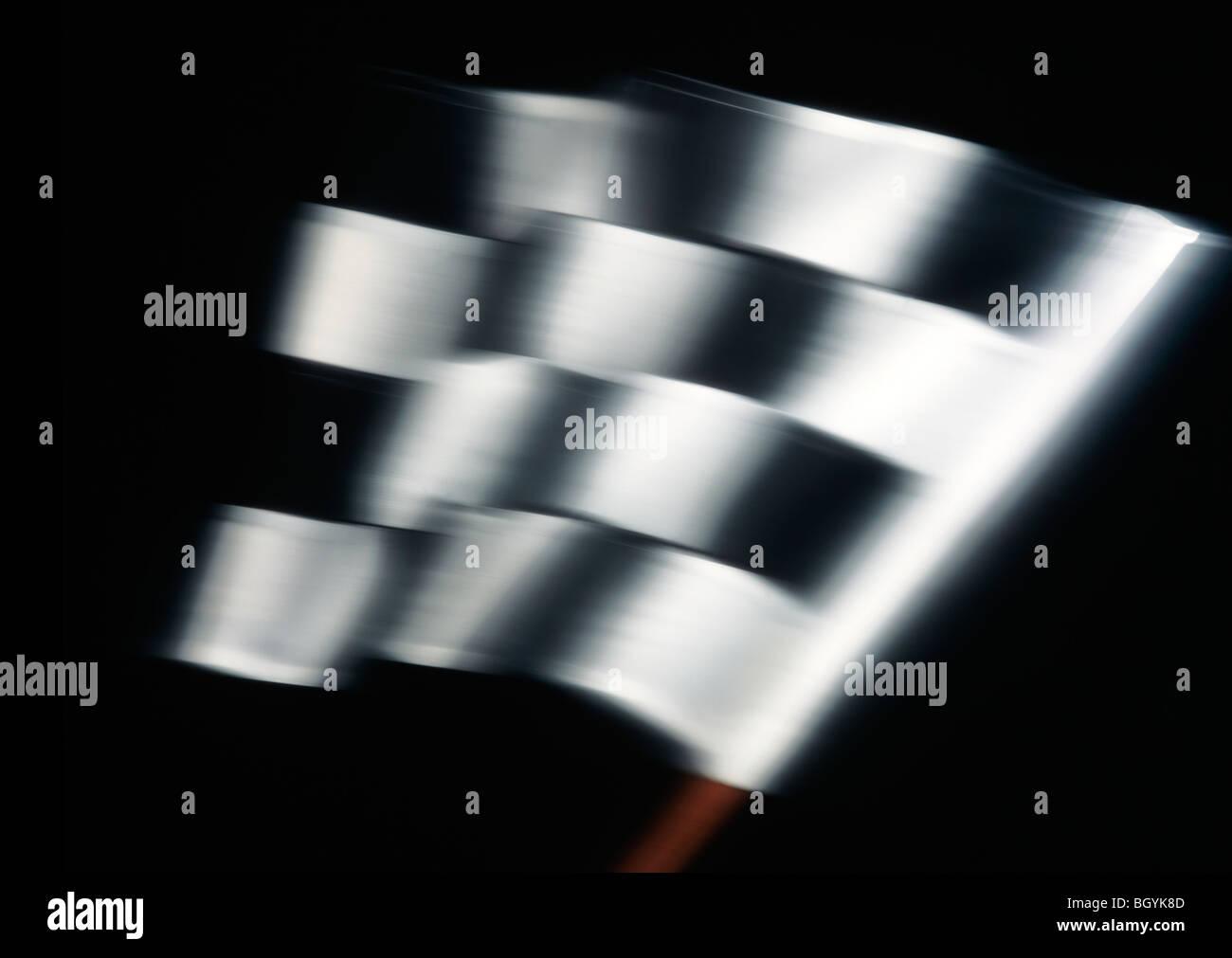 Drapeau à damier avec mouvement sur un fond noir Photo Stock