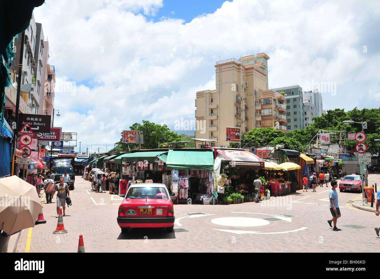 Boutiques en plein air, les panneaux publicitaires, les consommateurs, les taxis et les camions de livraison à Photo Stock